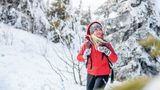 A woman in a red coat hikes through the trees in the snow