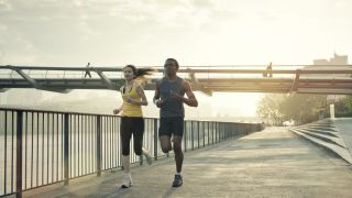 a man and woman run by the Thames River in London