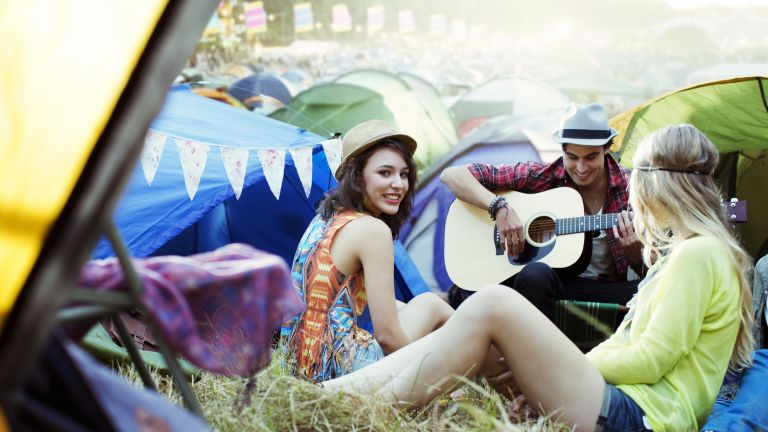 Best festival tents: a group of friends sit outside their festival tent on a music festival campsite
