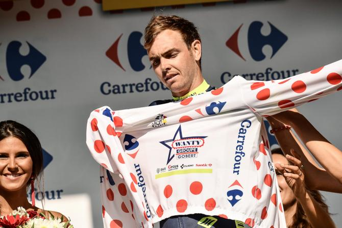 Dion Smith puts on the best climber's polka dot jersey on the podium after the third stage