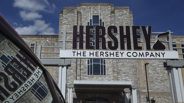 Signage is reflected in vehicle parked outside Hershey's headquarters in Hershey, Pennsylvania, U.S., on Friday, July 13, 2018.