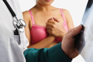 A woman waits nervously while a doctor looks at a mammogram.