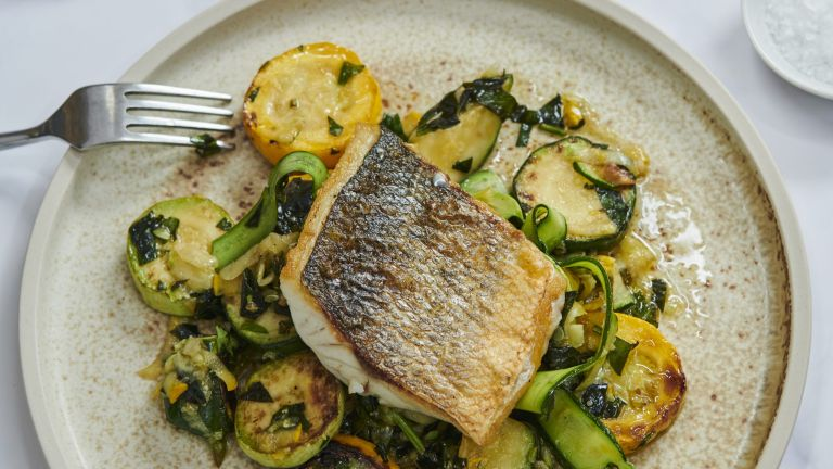 Pan fried sea bass fillet with herbed courgettes