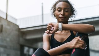 Woman resting after a run, checking her running watch