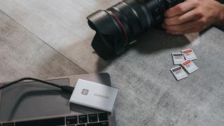 digital camera on floor alongside external hard drive and SD cards