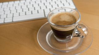 Cup of espresso by a computer keyboard