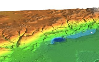 A lidar survey shows the entire ceremonial center stretching for 1.2 miles (2 kilometers) along a limestone ridge overlooking Laguna Ek'Naab (white spot), the sampling site for the paleoenvironmental study on the Maya.