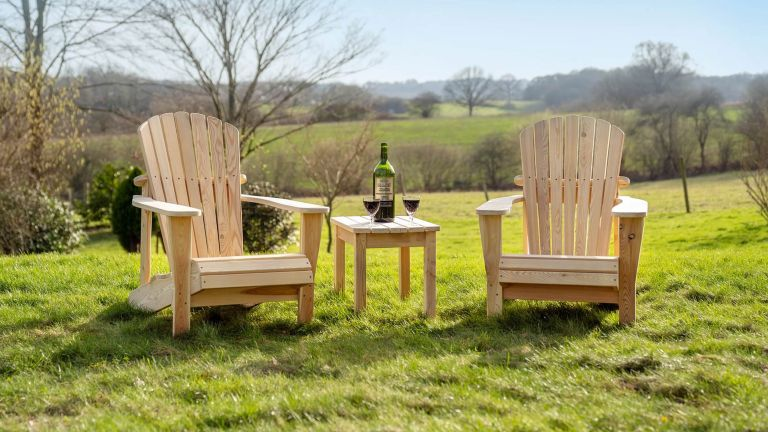 A pair of wooden Adirondack chairs on a grass lawn