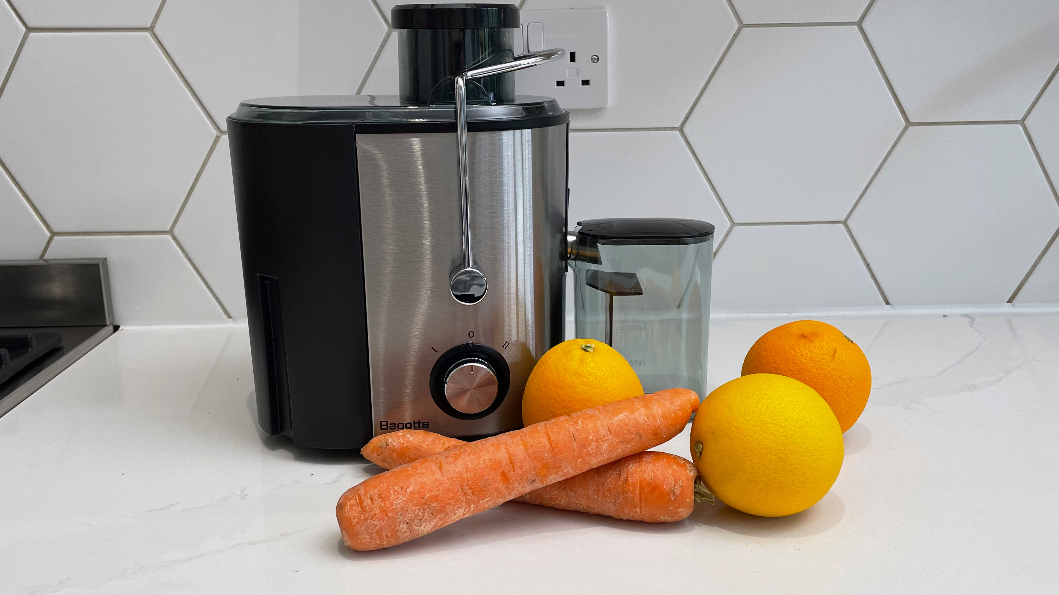 The Bagotte DB-001 juicer on a kitchen countertop next to some oranges and carrots ready to be juiced