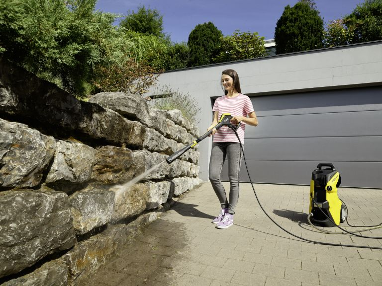 Woman using Kärcher K7 Premium smart control pressure washer to clean a stone wall