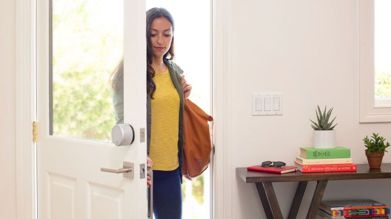 woman walking through door with the best smart lock which keeps her home secure
