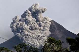 An image from October 2010 shows an earlier blast of dust out of the volcano.