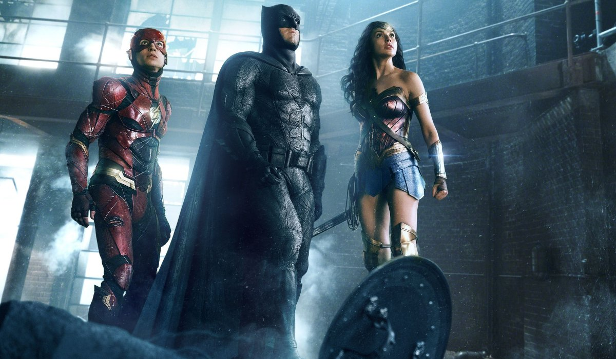 The Flash, Batman, and Wonder Woman looking up at a situation in Justice League.