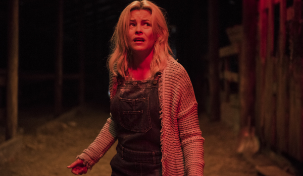 Brightburn Tori looking frightened in the barn, bathed in red light