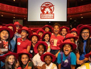 Kids wearing Carmen Sandiego gear and red hats smile and laugh under a banner displaying her logo