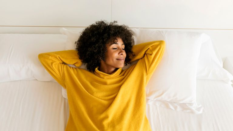 Smiling woman with her eyes closed lying on bed