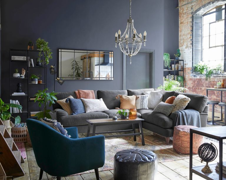 industrial boho style loft lounge living room with navy walls, blue sofa with textured cushions and accessories - dunelm