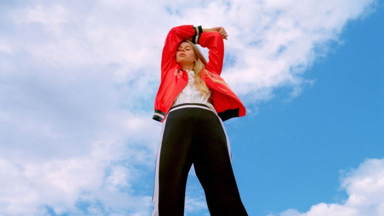 Young woman in fashionable clothing under a blue sky