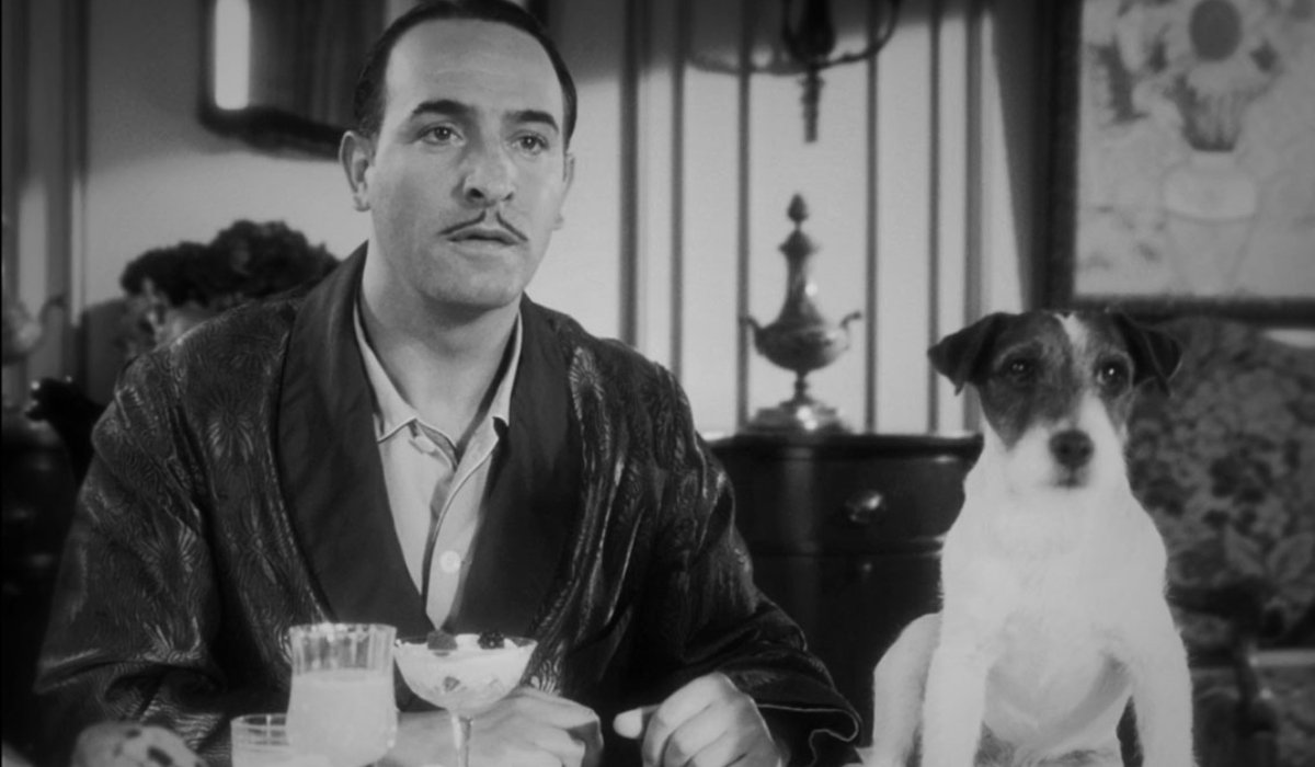 Jean Dujardin and Uggie sitting at the breakfast table in The Artist.