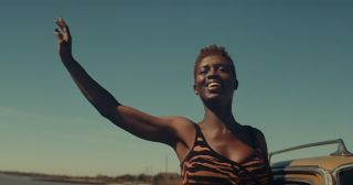 Jodie Turner-Smith waves in front of a blue sky