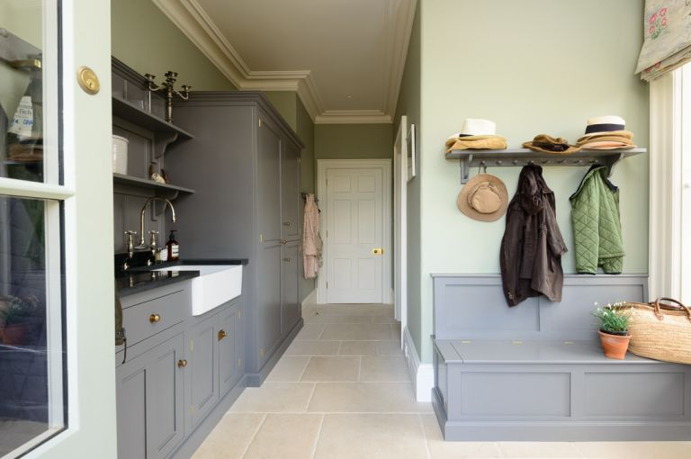 A large mudroom with grey storage and hooks for coats used as an example of designing a mudroom