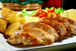 A plate of grilled chicken and potatoes