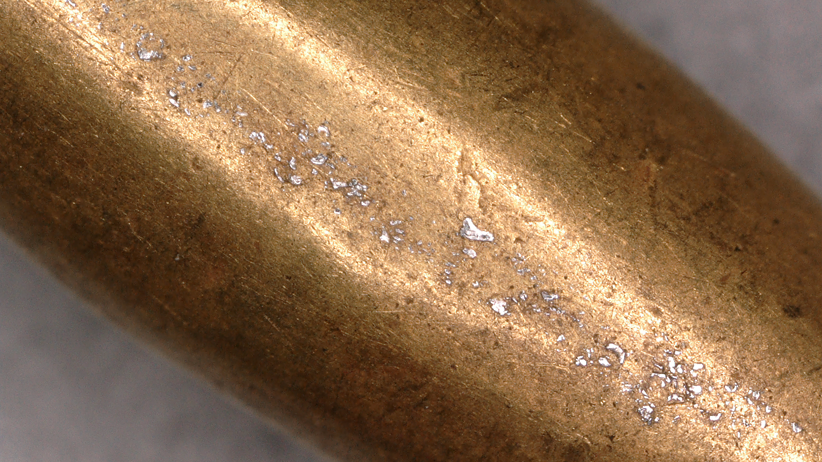 Analysis of light-colored spots on a gold bead from the cloak of Queen Puabi of Ur helps researchers trace the geological origin of the gold.