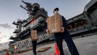 Sailors assigned to the aircraft carrier USS Theodore Roosevelt carry food supply boxes for sailors who either tested negative or are asymptomatic for COVID-19 and are staying at local hotels in Guam on April 7, 2020.