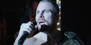 Stephen Amell talks into a microphone in the wrestling ring in Heels.