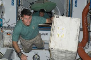 Astronauts Pack Up Space Shuttle Cargo Pod