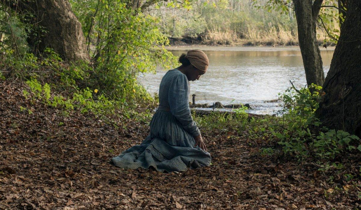 Harriet kneeling in the woods, by the water