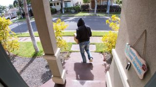 Staged photo of a 'porch pirate' stealing a package from a residence's front door, as captured by a video doorbell.