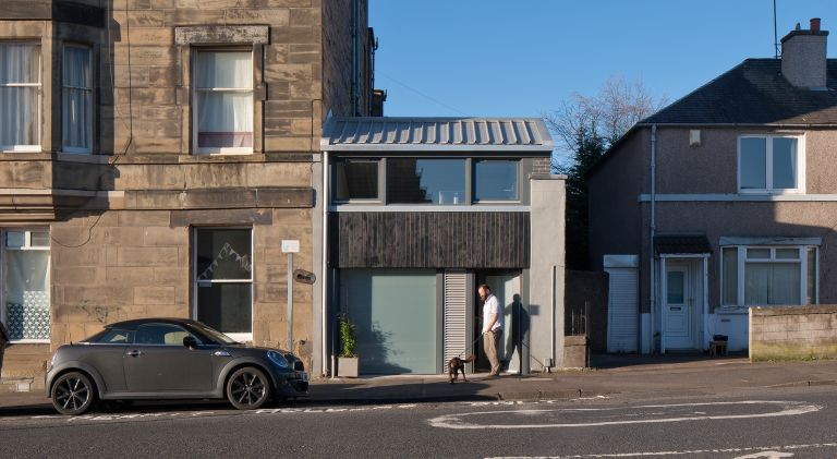 Former two-storey shop converted to a family home, with grey and black cladding