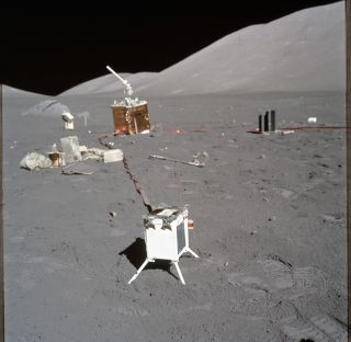 A photograph taken during Apollo 17 shows science experiments in the foreground and background with a debris pile including experiment wrappers and covers on the left.