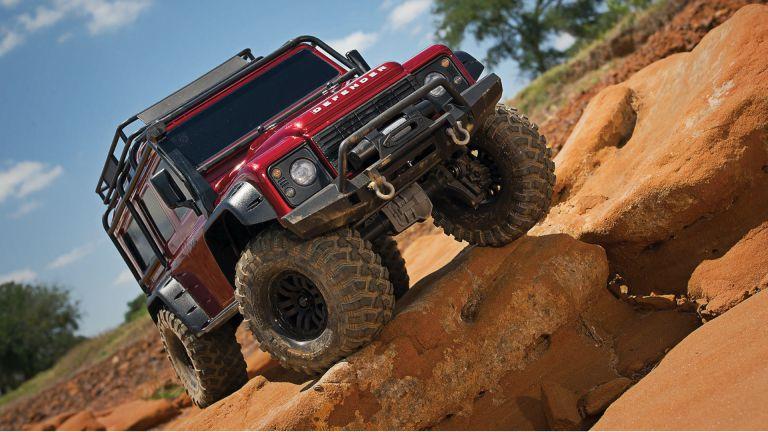 Red Land Rover Defender in desert-like terrain