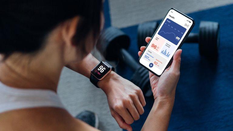 Woman looking at data on her fitness tracker and health app
