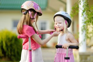 Girls putting on bike helmets