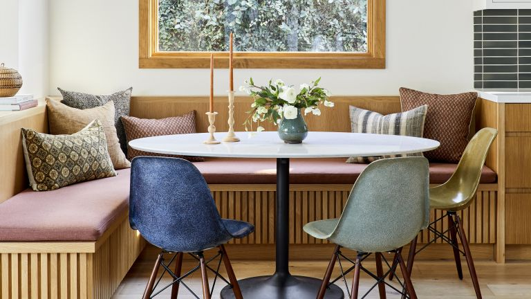 Samll dining room ideas with a white oak corner bench, round table and colored chairs
