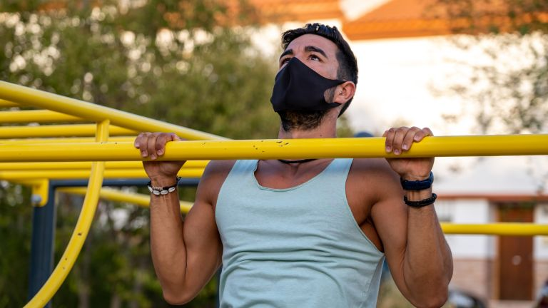 Man doing a pull up wearing a protective face mask