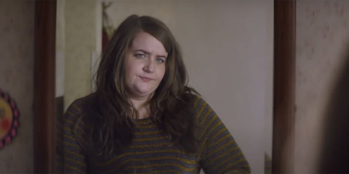 Aidy Bryant leaning against a doorway in a brown sweater on Shrill.