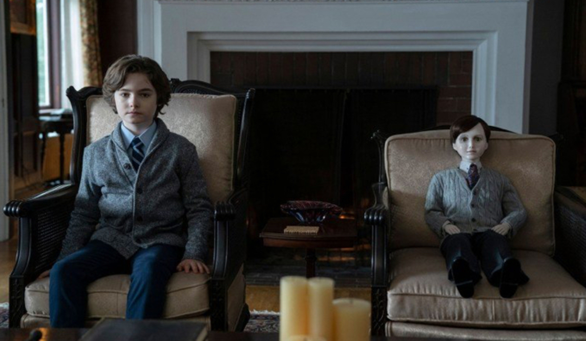 Brahms: The Boy II a young boy and a doll sit dressed identically in the living room