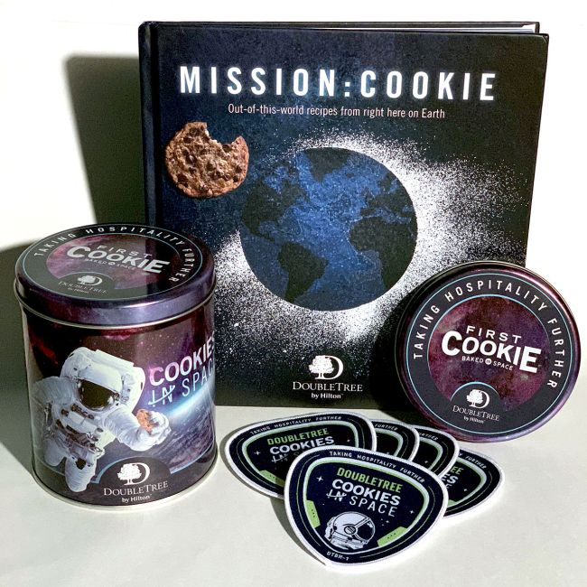 "DoubleTree by Hilton's ""Cookes in Space"" commemorative tin, ""Mission: Cookie"" cookbook and mission patch."