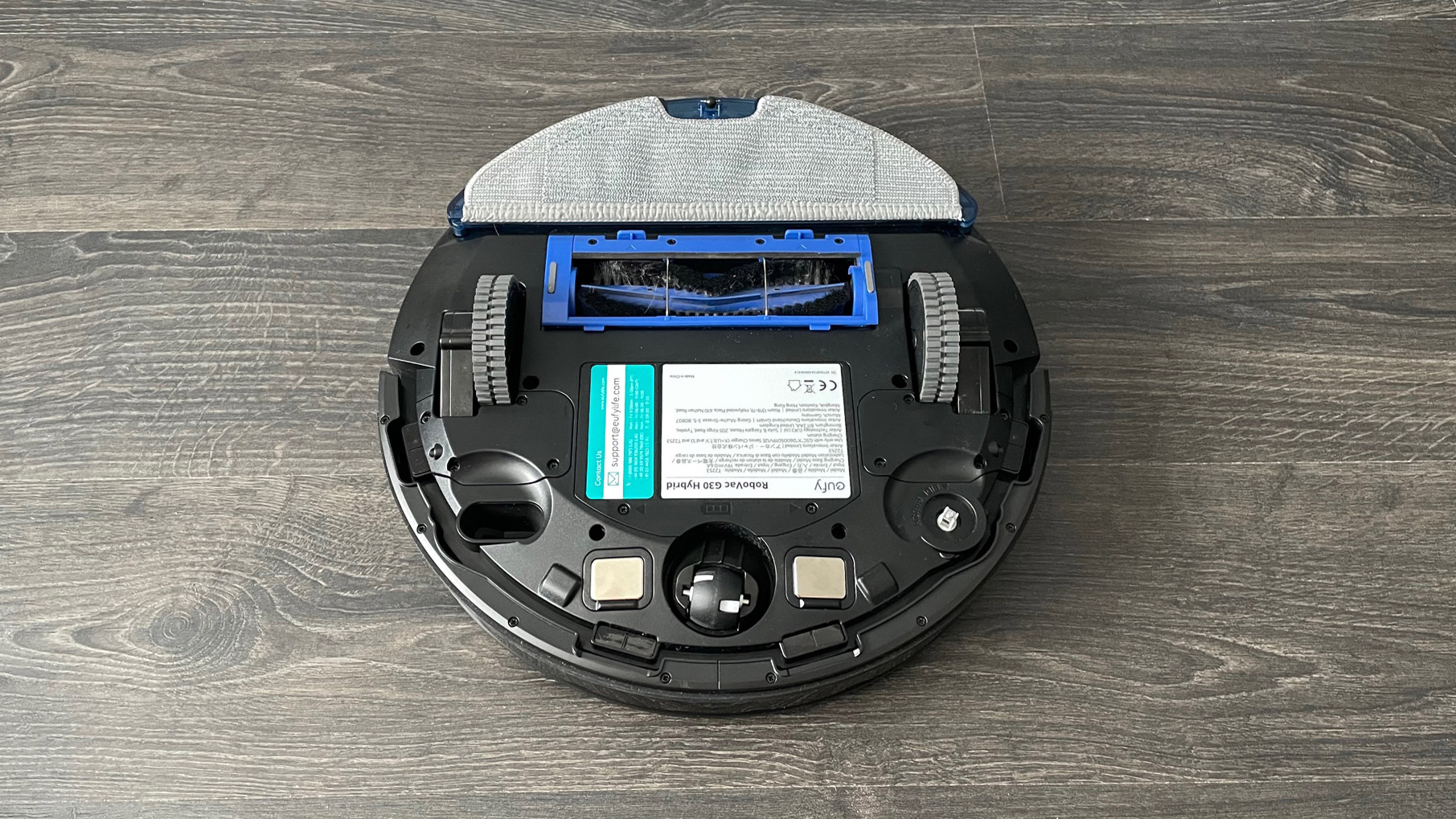 Eufy RoboVac G30 Hybrid upside down with the mopping pad attached on a wooden floor