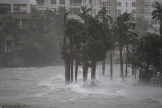 Water flowing out of the Miami River floods a walkway as Hurricane Irma passes through on Sept. 10, 2017, in Miami, Florida.