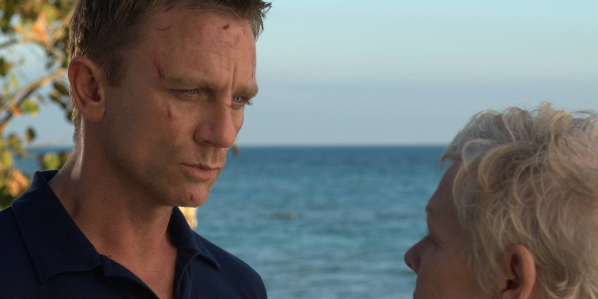Daniel Craig stands listening to Dame Judi Dench in front of the ocean in Casino Royale.