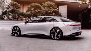 Side profile of the Lucid Air EV parked outside a modern house