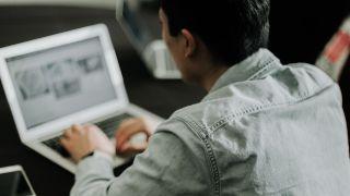 password recovery tool - man sat typing at laptop