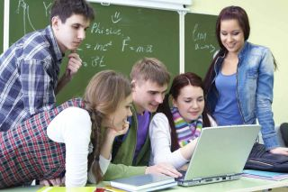 Teens looking at laptop computer in math class