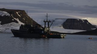 The Altai tugboat near a small landing craft.