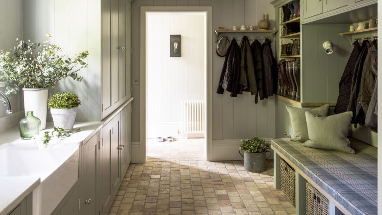 Country style boot room with Barbour jackets handing on coat rails